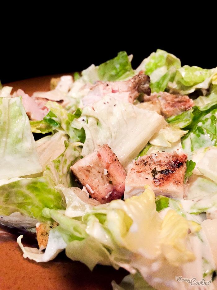 «Ensalada César», lechuga, queso, croutons y salsa César con jugoso pollo a la parrilla que ¡sabe a parrilla!